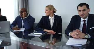 A Friendly Conversation Before Business Meeting/Business team is waiting for the start of the meeting. The men and the woman sit at the table. There is a relaxed conversation. The participants in a good mood, they are smiling and joking