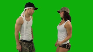 A girl and a guy dressed in military-style clothes dancing hip-hop battle