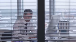 A Typical Day of a Businessman at the Office/ Businessman sitting at a desk and typing on a computer. He's in a good mood, because smiles slightly. His office is located behind a glass partition. The windows in the room are large and bright.