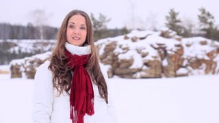 Beautiful girl in winter clothes talks on the phone and then smiles to the camera