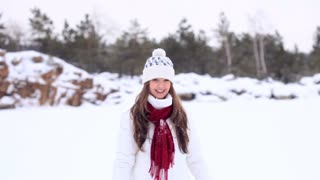 Beautiful girl in winter clothes throws a snowball into the camera!
