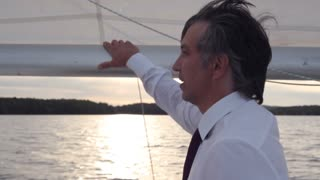 Business Project Nearing Completion/Sunset. Businessman on a yacht. Businessman looks into the distance. He shows the purpose of steering where to come. Behind his head we see the sail
