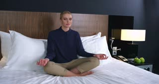Business woman meditating in the lotus position on the bed