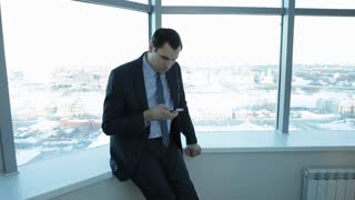 Businessman Chatting During a Break/smartphone, technology, communication, businessman, phone, man, mobile, chatting, office, business, internet, break, using, reading, browsing