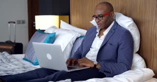 Businessman in Hotel Room/Businessman in a hotel room checks mail on a laptop. He feels himself comfortable on the bed and smiling from good news