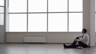 Businessman is talking on the phone in an empty office, he is stressed and depressed. His company went bankrupt