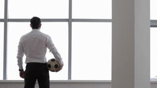 Businessman Plays with a Football Ball