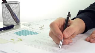 Businesswoman Analyzes Report/Businesswoman looks at the graphs and makes corrections. Close up