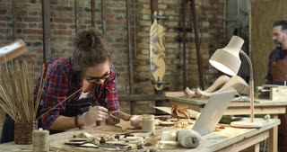 Busy Hipster Workshop/We see a busy workshop. The hipster girl on the foreground is painting wooden toys, and two men, young and middle-aged are making the cabriole table leg