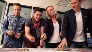 Designers at Work/A group of young designers led by the head are working on the project of design business center, private home, studio, shop, office. At some point in the office someone comes and the whole team smiling and greeting him.