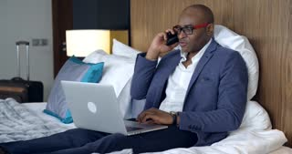 Difficult Telephone Conversation/Businessman in a hotel room. He is an African American. He is talking on the phone. Start a conversation is not very pleasant, something goes wrong. Businessman dissatisfied and makes desperate gestures