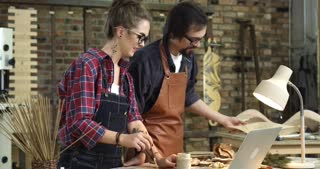 Easy Communication in Designer Studio/Two hipsters having a small talk during their work in a wood workshop. They are very positive and happy, smiling and making jokes. The man looks at the girls work.