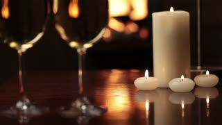 Glasses of champagne near fireplace and candles