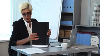 Heavy Weekdays of the Construction Company Accountant /Businesswoman's workplace. She examines the documents on her desk. She took from a shelf a folder with the last report, and compares its data with the data in his laptop