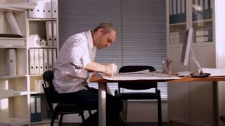 In the Architect's Office/The man most likely an architect or an engineer, sitting at the table and drawing the project of premises. We see a lot of folders with documents in his office