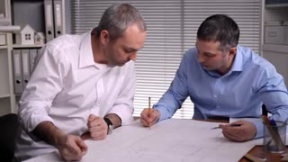 Joint development of the structural elements of the business center/When team work matters. The discussion of a construction project by two architects. They try to solve the problem. The blueprints are made on paper
