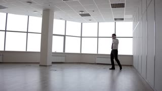 Nervous Conversation With Creditors in Bankruptcy/Businessman is talking on the phone in an empty office, he is stressed and depressed. His company went bankrupt
