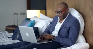 Online Shopping in the Hotel Room/Afro-american businessman is sitting in hotel bed, buying online. He's happy to have this service, it's very convenien
