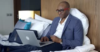 Online Shopping in the Hotel Room/Businessman in a hotel room. He sits on the bed and makes an online purchase in the online store. There's a chance that he's buying for a loved one. Businessman smiling