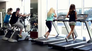 People Training in a Gym Using Treadmills and Exercise Bicycles