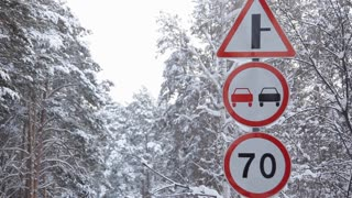 Prohibitory Road Signs on Winter Road/Prohibitory Road signs on winter road. Pine trees covered with snow. Snowing