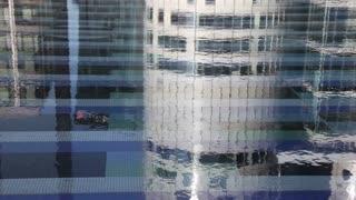 Reflections of buildings in water. Paris, La Defense. Medium shot