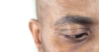 Slow Motion Shot Extreme Close-Up of a Brown Eye of an Afro-American Man/ He looks down the frame and then straight to the camera. He is relaxed