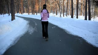 Steadycam shot of a girl jogging in the forest in winter and a guy outruning her