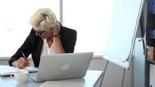 Stress at Workplace /Businesswomen takes off her glasses, turns and looks out the window.