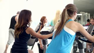 Training in a Gym, people training in a gym using elliptical cross and exercise bicycles.