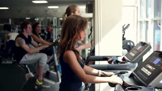 Training in a Gym, people training in a gym using treadmills and exercise bicycles