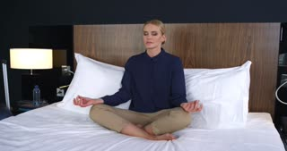 Business Woman Meditating in the Lotus Position on the Bed/ Business woman meditating in the lotus position on the bed. She think about successful negotiation and signing of the contract