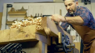 Cabinet Maker Planes Solid Wood in his Workshop/Cabinet maker planes the beech plank with a plane. He works in a small family joiner's shop. Slow motion