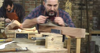 Cabinet - Maker's Handwork is Very Appreciated/Cabinet-maker is preparing a detail for the table made of beech. He's in the joiner's shop. In the background we see a young joiner polishing a cabriole table leg
