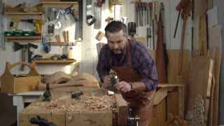 Carpenter Planes Solid Wood in his Workshop/ Cabinet maker planes the beech plank with a plane. He works in a small family joiner's shop