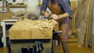 Carpenter Planes Solid Wood in his Workshop/Cabinet maker planes the beech plank with a plane. He works in a small family joiner's shop