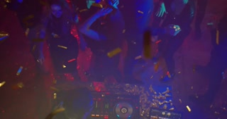 Dancing in a Nightclub. High Angle Shot. Young people dancing in the nightclub. Confetti are all around them. They are friends, celebrating Birthday party, or a New Year