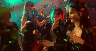 Dancing in the Confetti. Happy young women dancing energetically at a nightclub. It can be a New Year Party, or Birthday Party, as confetti are flying all around them