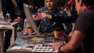 Designers at Work/A group of young designers led by the head are working on the project of design business center, private home, studio, shop, office. At some point in the office someone comes and the whole team smiling and greeting him