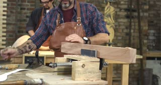Handwork Makes Cabinet Maker Happy/ Cabinet-maker is preparing a detail for the table made of beech. He's in the joiner's shop. In the background we see a young joiner polishing a cabriole table leg