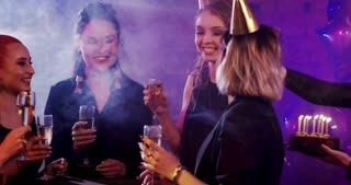 Here's Your Birthday Cake! Young woman is celebrating her birthday, her friends give her a birthday cake. They are celebrating in a nightclub