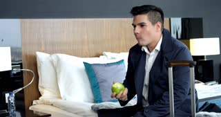 My First Business Trip Was a Success/ Young businessman eats an apple right after arriving to his hotel room during the business trip