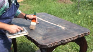 New Life of an Old Table. DIY woodworking/ The cabinet maker restores the larch table. He polishes the wood carefully to put any roughness. Sound on