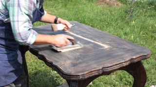 New Life of an Old Table/ The cabinet maker restores the larch table. He polishes the wood carefully to put any roughness. Sound on