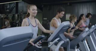 People training in a gym using treadmills and elliptical cross