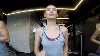 Young Woman Running on a Treadmill (Slow motion)/Just a day in a fitness club. People are running on a treadmill, we can see them from the monitor view (GoPro used)