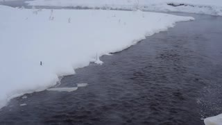 Winter River With Snowdrifts/A small river flowing among snow-covered coast. You can hear the murmur of water