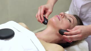 Woman Enjoying Stone Therapy/ Female Receiving a Relaxing Massage Treatment