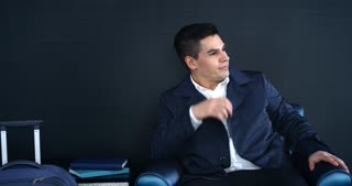Young Manager's Disturbing thoughts  Before Business Trip/A young businessman in a hotel room waiting for a taxi. He sits in a chair, wearing his coat. He is completely ready for the trip