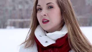 Young woman blows snow at camera.